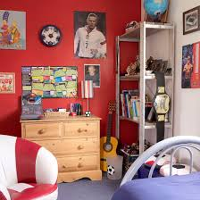 Boys' bedroom with striped armchair and red feature wall