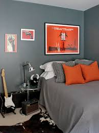 gray and orange bedroom. example of a small trendy carpeted bedroom design in london with gray walls and orange d