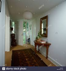 oriental rug on carpet. Oriental Rug On Sisal Carpet In Traditional White Hall With Mirror Above Antique Console Table R
