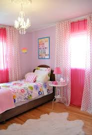 crystal chandeliers lamp over white bed connected by pink polka window curtains and pink wall theme