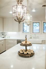 french country kitchen features a pair of white french tole chandeliers illuminating a center island topped with white quartz and a rustic tiered dessert