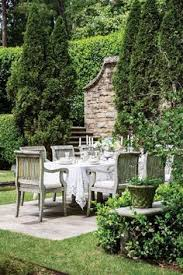 french farmhouse and french country living outdoor dining area is rustic yet elegant formal yet cozy lush greenery surround the dining table and chairs