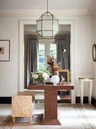 below a french lantern a burl wood table anchors the light filled entryway suzanne painted the baseboards a dark charcoal to define the architectural