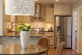 Contemporary monochromatic kitchen design with ivory kitchen cabinets,  black stone countertops, kitchen island peninsula, subway tiles backsplash,  ...