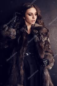 brunette woman in luxurious fur coat stock photo