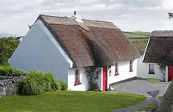 traditional thatched cottage with red door in Tully Cross in Connemara,  Ireland