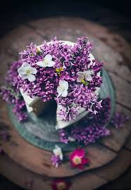 a spring wedding cake covered in lilac flowers and blossom