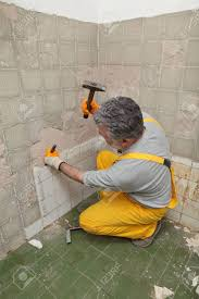worker remove demolish old tiles in a bathroom with hammer and chisel stock photo