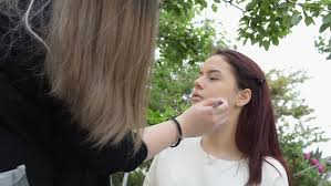 beautiful with her makeup artist apply makeup outdoor scene hd stock video clip
