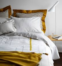 gold unstandard bold stripes commingle with indian inspired sheets and a quirky duvet cover