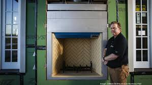 tom raver president of fireplace distributors is shown at an installation project in a
