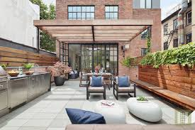 a glass wall on the first floor of the home opens directly to a sprawling back patio the outdoor space is outfitted with a kitchenette grilling station