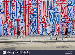 local people walking to work past a colourful mural painted by local people walking to work past a colourful mural painted by retna on the bowery mural