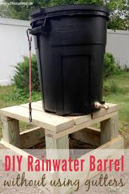 diy trash can rain barrel with a homemade wooden stand serving as a gutterless rain
