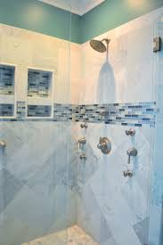 beautiful walk in shower with gray ceramic tile with aqua and turquoise blue accent tile