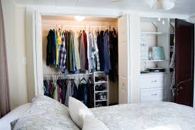 White Closet Bedroom With Doors Near Bed And Pillows
