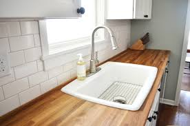 subway kitchen backsplash tile and butcher block countertop with white drop in sink a photo