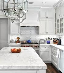 white kitchen features white cabinets paired with white marble countertops and white subway tile backsplash accented with dark grout
