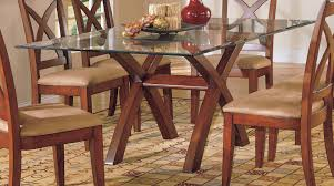 rectangle glass top dining table with double x brown wooden bases on brown rug