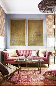 design ideas betty marketing paris themed living: tufted raspberry sofa in pattern packed living room with tapestry on wall