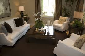 corner living room table. a modestly sized living room with two round end tables. one table is between the corner o