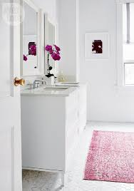 contemporary white bathroom with pink overdyed rug on marble hexagon tiles