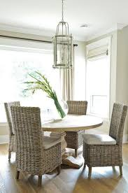 round salvaged wood dining table with wicker dining chairs transitional dining room