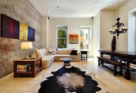 artwork on exposed brick wall and glass waterfall coffee table with faux cowhide rug and dark