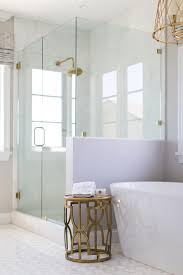 a freestanding oval bathtub is accented by a brass table under a gold cage chandelier