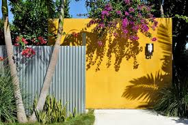 miami mustard yellow paint exterior contemporary with gold wall l outdoor lights and sconces house numbers