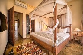 Amani Luxury Apartments: Bedroom With Lamu Inspired Poster Bed And Wood  Finishes.