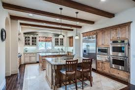 Beautiful traditional kitchen with two islands, decorative woodwork,  exposed beam ceiling and wood plank