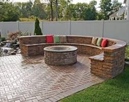 herringbone clad brick patio with a fire pit and a round bench of brick