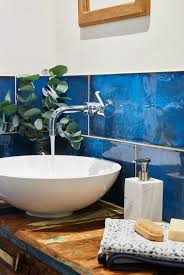 wooden bathroom vanity wooden top white large bowl shape sink potted plant blue large tile accent wall hand towel brush soap