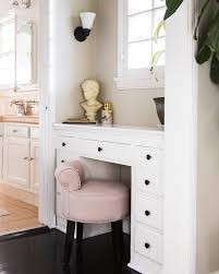 dressing table nook below window with built in white dressing table accented with black hardware with a pink vanity stool tucked under the counter