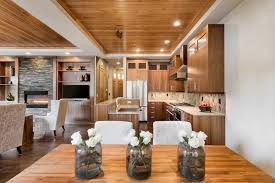 this kitchen boasts wooden cabinetry and kitchen counters matching the hardwood flooring and tray ceiling with
