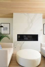 the master suite is fit to be in a high end hotel with its own fireplace with marble surround and cushy seating the veining on the calacatta porcelain thin