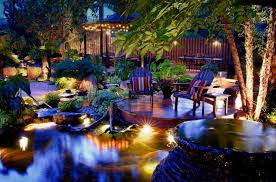 Paradise landscape lighting Accent Tropical Yard With Wooden Deck Stone Flooring Yellow Lighting Under The Plants And The Hayneedle Your Backyard With Paradise Lightings Decohoms