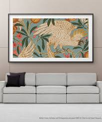 the frame hanging on a wall in a living room above a white couch and plants