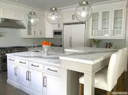 amazing kitchen features three clear glass globe pendants illuminating a white center island topped with statuary marble fitted with a small corner prep