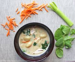 bowl of dairy free en and gnocchi soup surrounded by carrots celery and