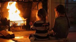 Two children heating at fireplace