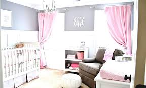 baby girl nursery room laminate oak wood flooring beige wool carpet comfortable fabric couch with ottoman pink storange bench white upholstered swivel chair