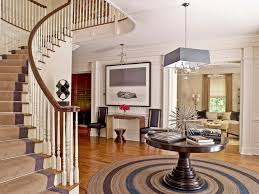 splashy round foyer table in entry transitional with half circle driveway next to banister alongside foyer table and grey carpet