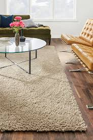 sophisticated brown room and board rugs and glass coffeetable plus beige sofa