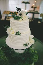 Simple Two Tier Wedding Cake Covered In Real Blossoms And Greenery