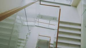 Office Stairs Top View Of Two Businessmen Meet At Staircase In Modern Office