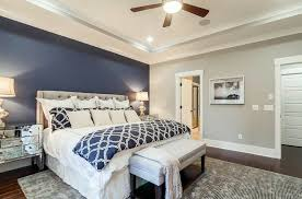 master bedroom with light gray walls and dark blue accent wall behind tufted bed