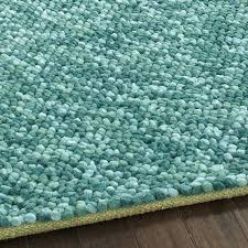 the pebbles rug in teal is a handwoven felted wool with soft thick pile comprised of felted wool rugs