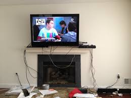 interior white accent wall with mounting tv above fireplace and and mounting tv above fireplace
